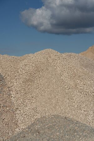 Mountains of sand and stone at a construction site on a background of blue sky with clouds on a sunny day