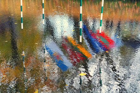 Reflection of national flags in the waves of the city canal at the competition in Riga on kayaks with gates