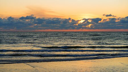 The sun sets to the horizon of the Baltic Sea with the reflection of clouds in the water Stock fotó