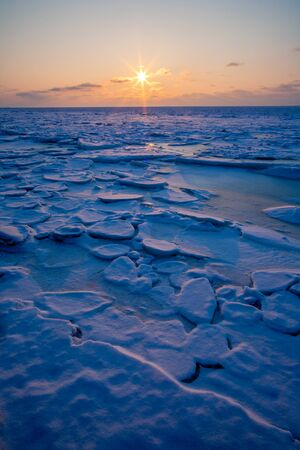 Sunset in the orange sky over the blue ice of the Baltic Sea in winter