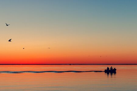 Fishing boat leaves the bay at sea for fish in the fall at dawn. Nida, Neringa, Lithuania