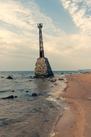 Old lighthouse Kurmrags on the sandy shore of the Baltic in spring. Latvija