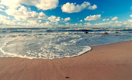 Storm on the sandy beach of the Baltic Sea on a sunny day with clouds on a blue sky. Latvia