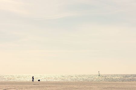 Lonely person on the beach over sea. Spring walks on a sunny day on the sandy Baltic beach in Estonia