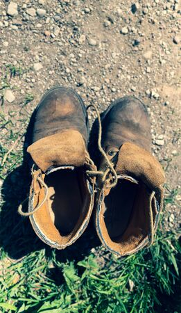 Old leather shoes with laces stand on the ground. Near green grass with stones. Imagens