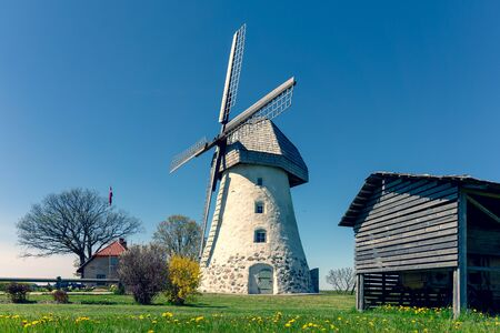 Ancient mill with wings on a green hill of Latvia in spring. Near the mill is a nest of storks. Gauja National Park. Latvia