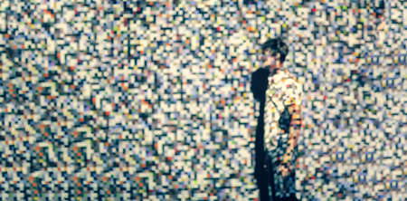 The man on the background of the projection of colored pixels. Pixels are chaotic in shape and color.