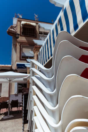The chairs are stacked on top of each other at the closed summer city cafe. Summer sunny day on the Mediterranean coast of Spain