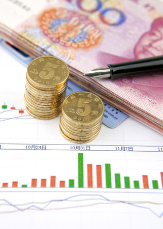 bankcard: Coins,chinese banknotes,pen and credit card on bar graph Editorial