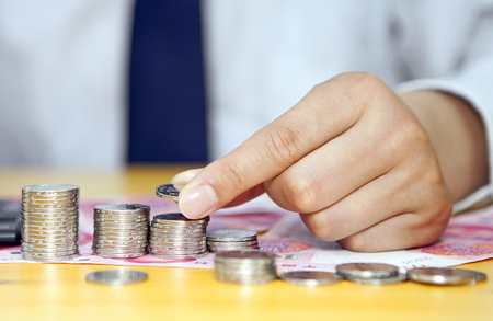 thrifty: Male hand putting renminbi coins into columns Stock Photo