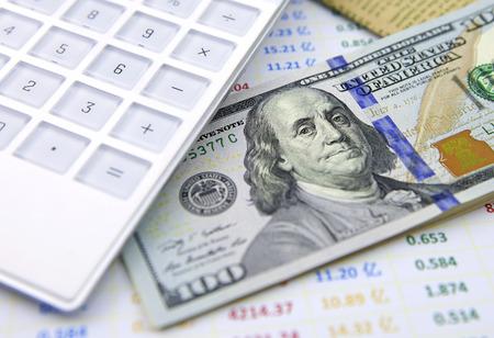 data sheet: Dollar banknotes with calculator on data sheet Stock Photo
