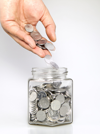 into: Man putting coins into jar for savings