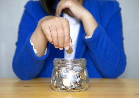 into: Woman putting coin into jar