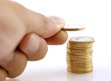 depositing: Stack of coins with a hand adding one more coin Stock Photo