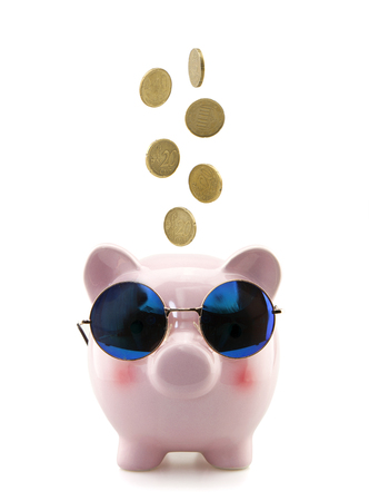 Piggy bank with glasses and falling coins Imagens