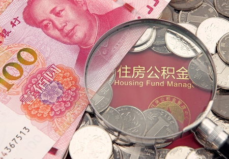 housing lot: A lot of china yuan and magnifier on the background of housing accumulation fund bankbook Editorial