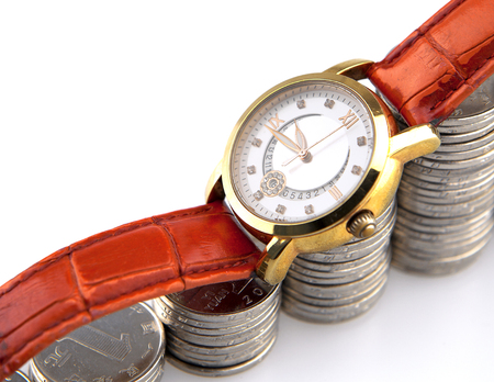 Golden wrist watch on rising pile of silver coins