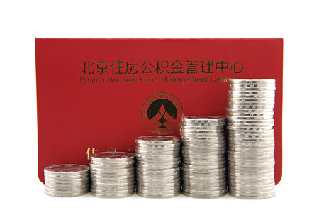 richer: Stacks of silver coins with housing accumulation fund bankbook