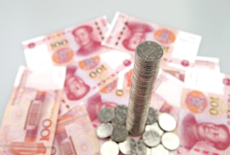 Tall tower of coins with china yuan banknotes Stock Photo