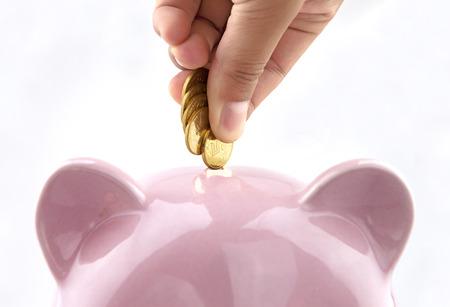 economise: Save money with piggy bank Stock Photo