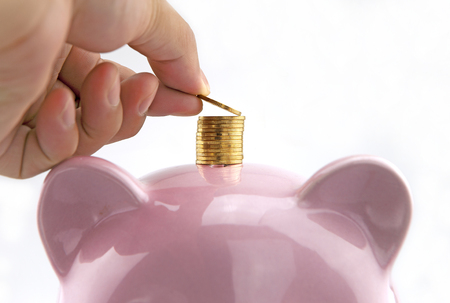 economise: Hand deposit money on the top of piggy bank