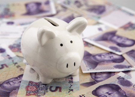 economise: Piggy bank on a pile of china five yuan banknotes