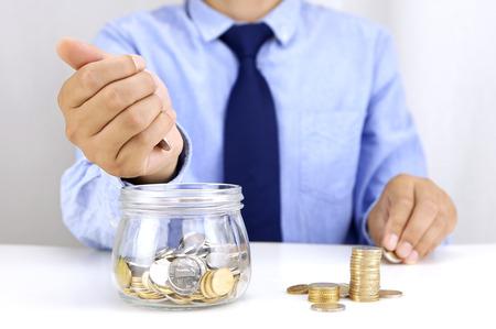 depositing: Young man depositing money in glass jar