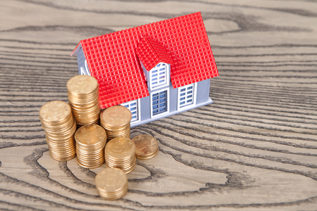 golden rule: Small house models and a pile of coins Stock Photo