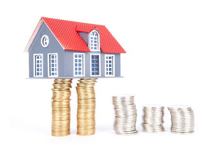 golden rule: A house model raised by coins Stock Photo