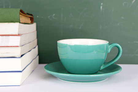 A cup of coffee and a pile of books