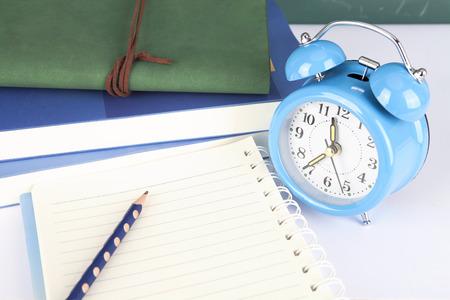Alarm clock, book, pencil and diary on table Lizenzfreie Bilder