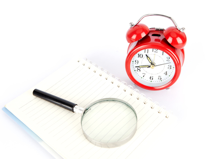 Alarm clock, magnifying glass and diary book