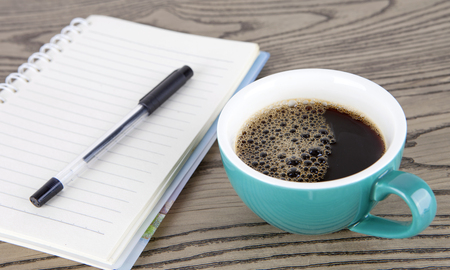 A cup of coffee and a ledger Stock Photo
