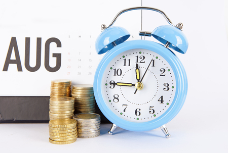 Financial concept with coin stacks and a blue alarm clock Stock Photo
