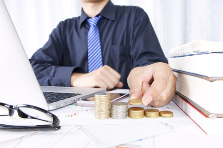 Close up view of investor sitting in front of the laptop with stack of coins Stock Photo