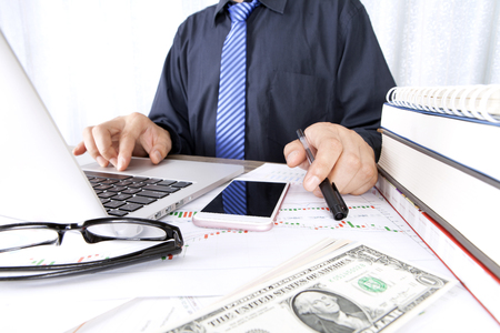 Investment businessman sitting in front of a laptop planning
