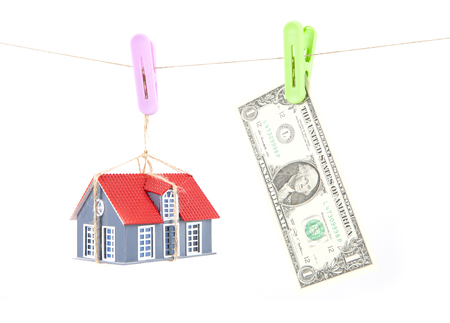 A model house hanging on a thread with a dollar bill on white background