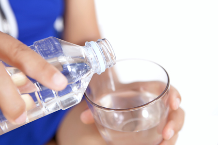 Pour mineral water into glass cup