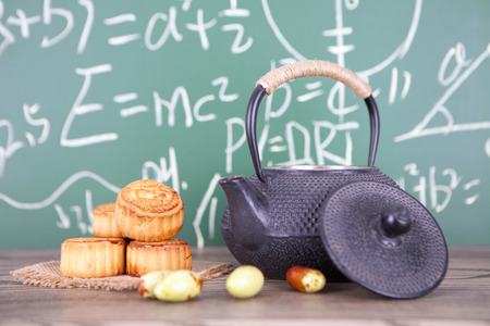 A teapot and moon cakes on the wooden table Stock Photo
