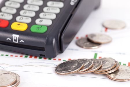 Card terminal and scattered dollar coins Stock Photo