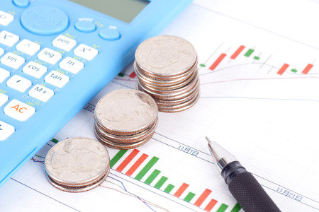 Financial investment plan with a pen, coins and calculator Stock Photo