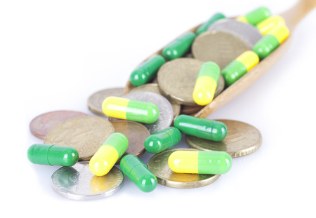 Capsules and coins on white background