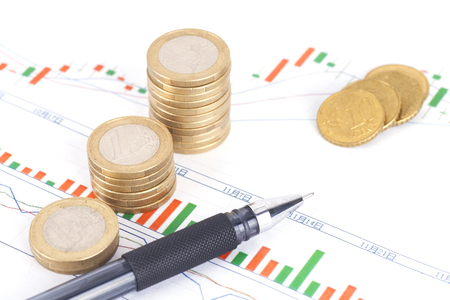 Financial investments concept with a pen and coin stacks