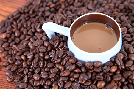 Hot coffee served in a cup with coffee beans background Stock Photo