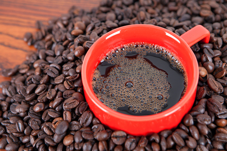 Coffee served in a cup with coffee beans as background