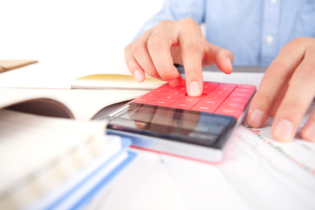 Accountant at work using a calculator close up view