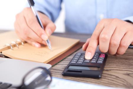 Financiële analist op het werk die een calculator dichte omhooggaande mening gebruiken