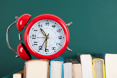 Reading time concept with an alarm clock and a stack of books