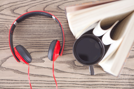 book, earphone and coffee on wooden desk Stock Photo