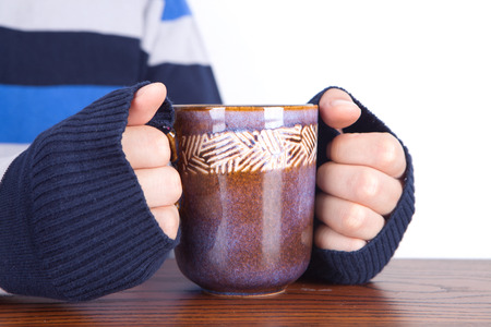 A person who warms hands with hot water in winter